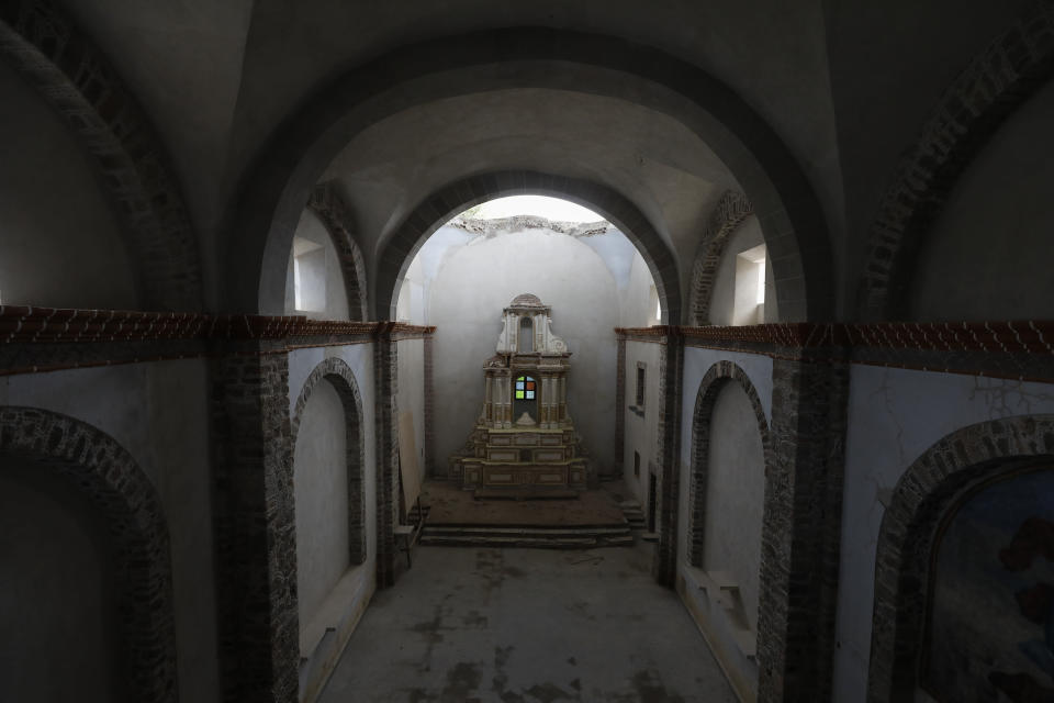 The damaged altar stands below a collapsed section of the vault, now shielded by a temporary metal roof, at the former San Guillermo Convent, where restoration work is underway three years after an earthquake damaged its church and adjacent cloisters, in Totolapan, Morelos state, Mexico, Tuesday, Oct. 13, 2020. Experts restoring buildings and monuments here have faced every kind of challenge: how to replace a bent old steel support completely encapsulated inside a slender stone column hundreds of feet tall; how to fix foundations sunk in swampy soil; how to restore church bell towers that are central to village life. (AP Photo/Rebecca Blackwell)