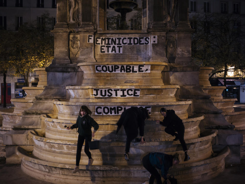 """From left to right, Pauline, Clivia, France and Lea paste a slogan on a fountain reading """" Femicides : guilty state, accomplice justice"""" in central Paris. About 300 women across France pasted slogans at the same time overnight from Sunday to Monday on courthouses in 27 different French cities to denounce the alleged inaction of the French government and demanding justice about femicides. (Photo: Kamil Zihnioglu/AP)"""