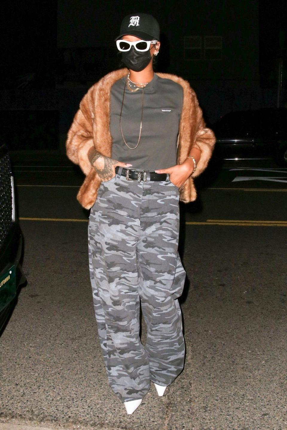 <p>Rihanna adds a glam touch to camo pants with white heels and a fur coat for dinner at Giorgio Baldi in Santa Monica on Tuesday. </p>