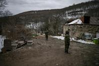 Armenian soldiers stand guard outside houses in Shurnukh village. Up until a few months ago the nearest Azerbaijani presence was dozens of kilometres away