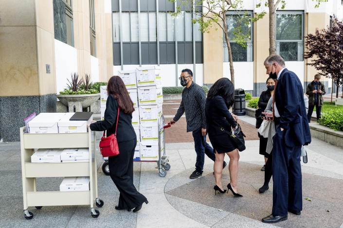 Members of Apple's legal team roll exhibit boxes into the Ronald V. Dellums building in Oakland, Calif., as the company faces off in federal court against Epic Games on Monday, May 3, 2021. Epic, maker of the video game Fortnite, charges that Apple has transformed its App Store into an illegal monopoly. (AP Photo/Noah Berger)