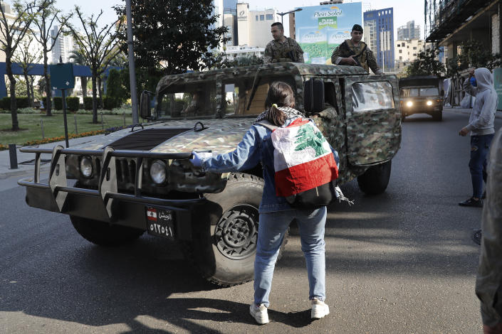An anti-government protester forces an army vehicle to turn back during a protest against the deepening financial crisis, in Beirut, Lebanon, Tuesday, April 28, 2020. Hundreds of protesters in Lebanon's northern city of Tripoli set fire to two banks and hurled stones at soldiers, who responded with tear gas and batons in renewed clashes triggered by an economic crisis spiraling out of control amid a weeks-long virus lockdown. (AP Photo/Hussein Malla)