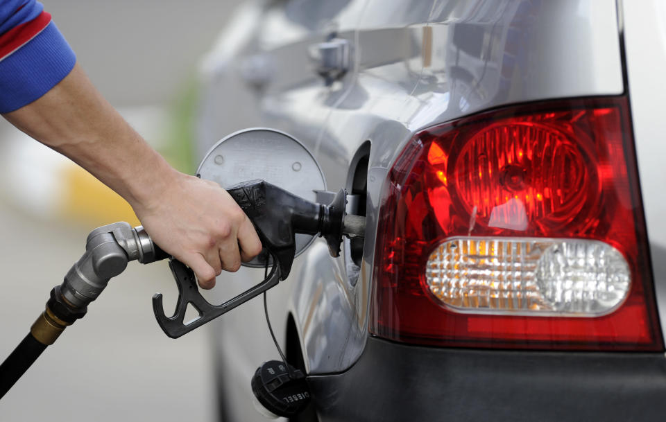 A man pumps petrol at a service station in Melbourne, Monday, Aug. 27, 2012. (AAP Image/Julian Smith)