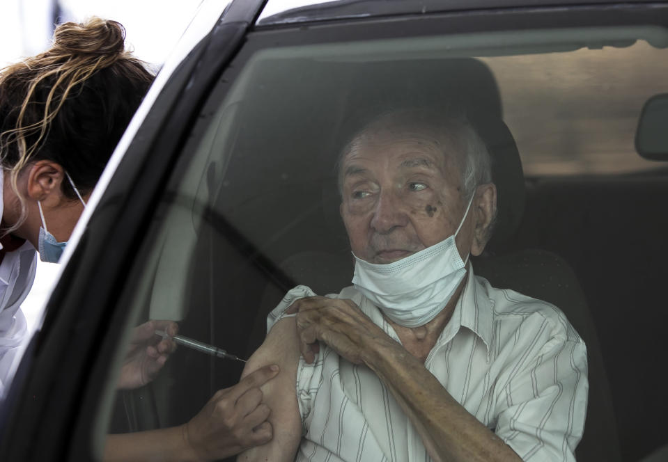 An elderly man receives a dose of the China's Sinovac Biotech COVID-19 vaccine at a drive-thru vaccination site in the Sambadrome, in Rio de Janeiro, Brazil, Saturday, Feb. 6, 2021. In a normal year, Rio's Sambadrome would be preparing for its great moment of the year: the world's most famous Carnival parade. But a week before what should be the start of Carnival, the pandemic has replaced pageantry. (AP Photo/Bruna Prado)