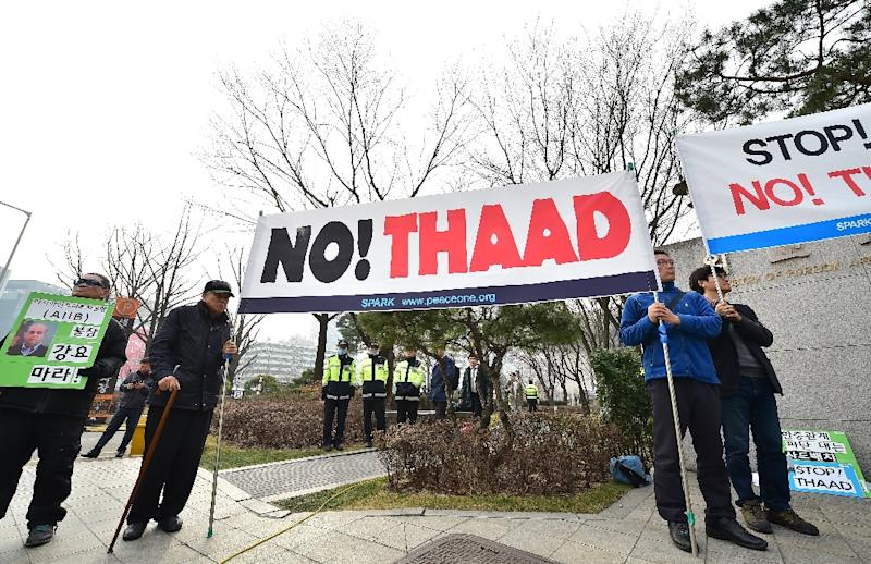 Anti-war activists hold a banner demonstrating against the Terminal High Altitude Area Defense (THAAD) anti-ballistic missile system, outside the Foreign Ministry in Seoul, on March 17, 2015 (AFP Photo/Jung Yeon-Je)