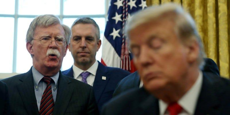 FILE PHOTO: U.S. President Donald Trump listens as his national security adviser John Bolton speaks during a presidential memorandum signing for the