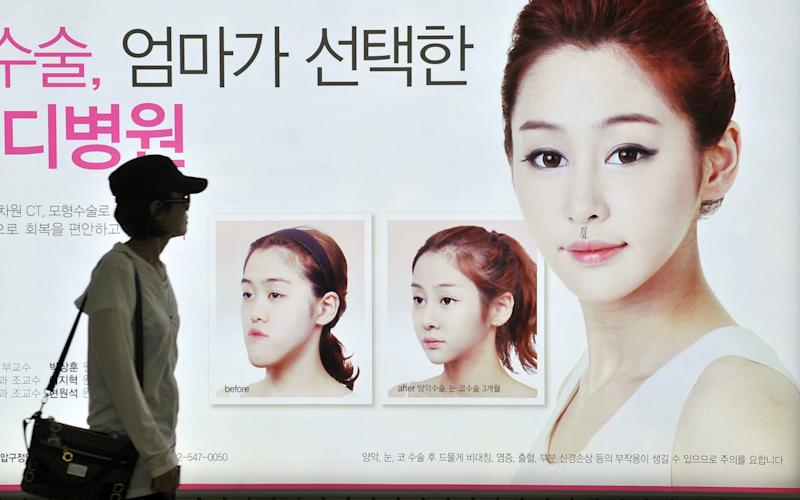 A South Korean woman walking past a street billboard advertising double-jaw surgery at a subway station in Seoul - AFP