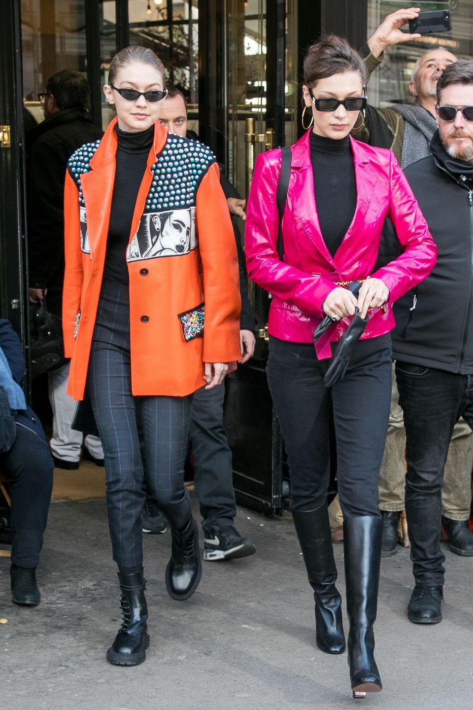 """<p>Gigi in a slightly-oversized orange leather jacket adorned with bright blue studs and comic motifs from Prada's Spring 2018 collection, paired with a simple black turtleneck, plaid pants, and side-laced combat boots.</p><p>Bella wearing a fitted magenta patent leather blazer by Georgine, cinched at the waist with a gold vintage Chanel chainlink belt from <a href=""""https://www.whatgoesaroundnyc.com/chanel-quilted-cc-chain-belt-q6a01m17db078.html"""" rel=""""nofollow noopener"""" target=""""_blank"""" data-ylk=""""slk:What Goes Around Comes Around"""" class=""""link rapid-noclick-resp"""">What Goes Around Comes Around</a>, a similar turtleneck, black pants, and knee-high boots while out in Paris.</p>"""