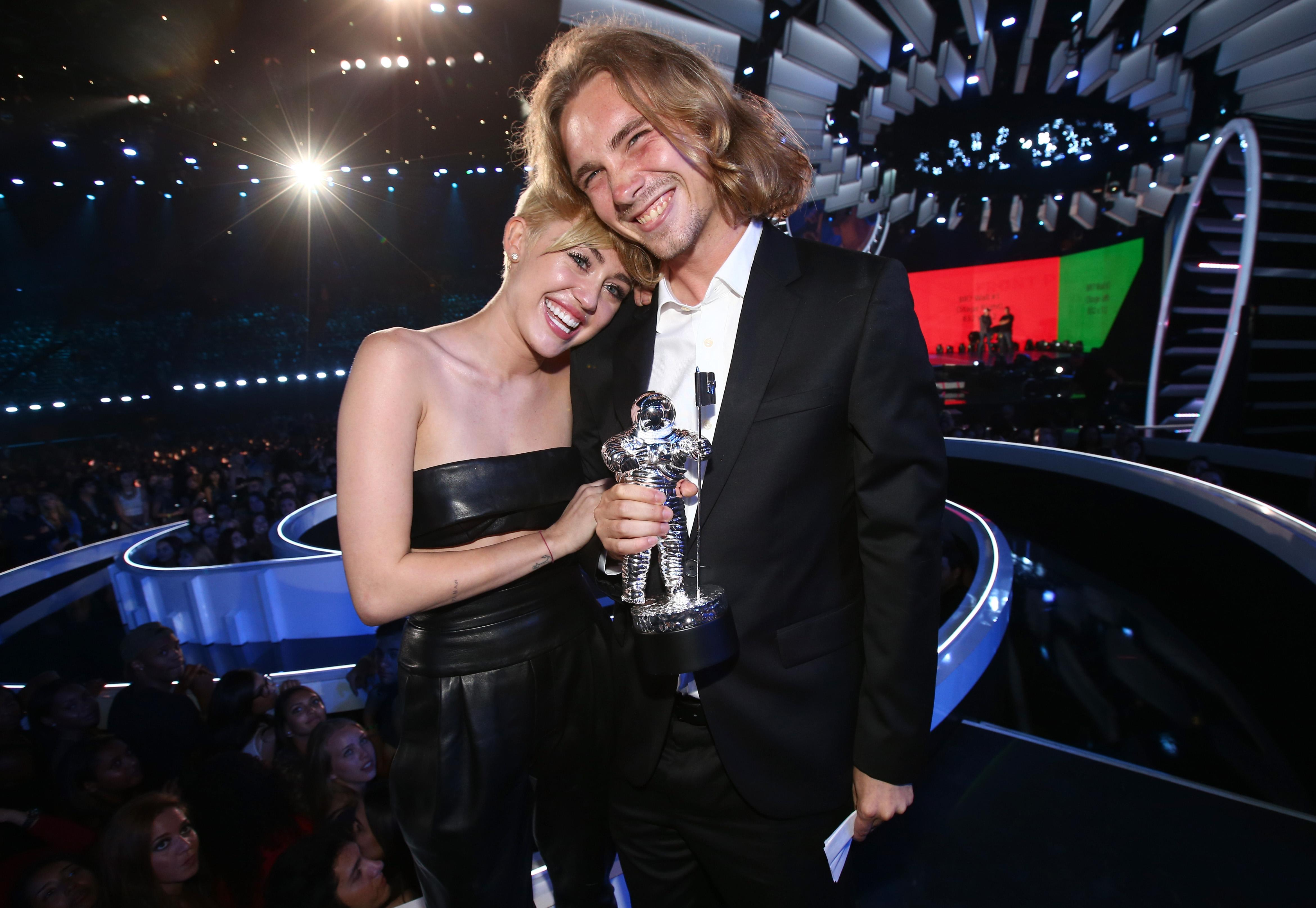 Miley Cyrus attends the 2014 MTV Video Music Awards with a homeless youth.
