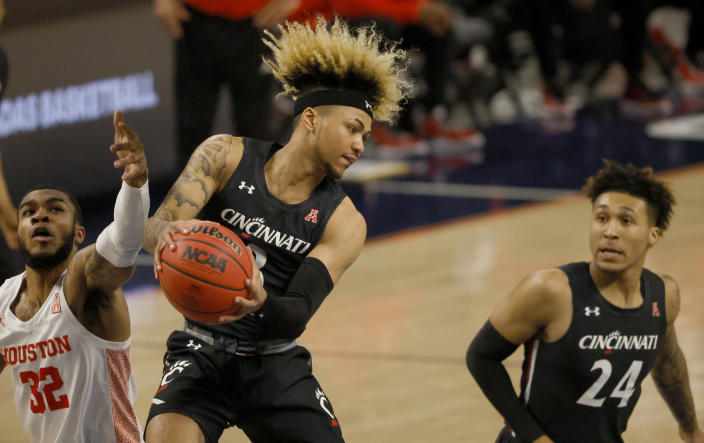 Cincinnati guard Mike Saunders (3) rebounds as Houston forward Reggie Chaney (32) and teammate Jeremiah Davenport (24) look on during the first half of an NCAA college basketball game in the final round of the American Athletic Conference men's tournament Sunday, March 14, 2021, in Fort Worth, Texas. (AP Photo/Ron Jenkins)