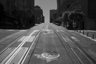 Empty cable car tracks lead up to Nob Hill as a person crosses California Street between the Mark Hopkins and Fairmont hotels in San Francisco on May 1, 2020. Normally, the months leading into summer bring bustling crowds to the city's famous landmarks, but this year, because of the coronavirus threat they sit empty and quiet. Some parts are like eerie ghost towns or stark scenes from a science fiction movie. (AP Photo/Eric Risberg)