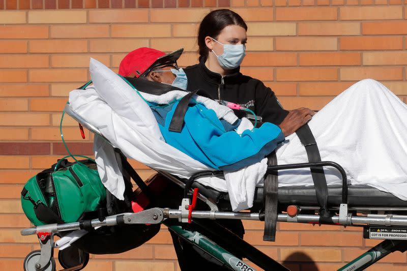 Healthcare worker wheels patient on stretcher into Wyckoff Heights Medical Center during outbreak of coronavirus disease (COVID-19) in New York