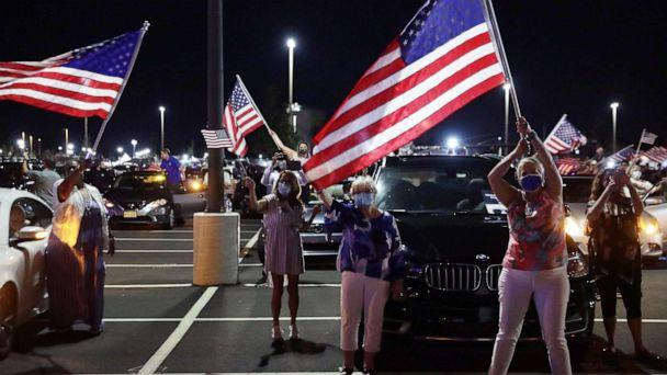 PHOTO: Supporters celebrate as they watch from a parking lot outside Chase Center in Wilmington Del., as former Vice President Joe Biden gives his acceptance speech during the Democratic National Convention, Aug. 20, 2020. (Alex Wong/Getty Images)