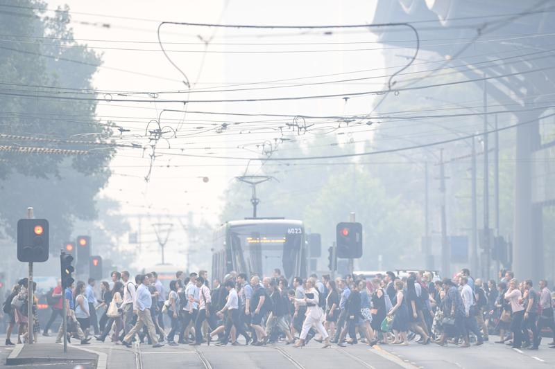 Morning commuters are seen through smoke haze from bushfires in Melbourne, Tuesday. Source: AAP