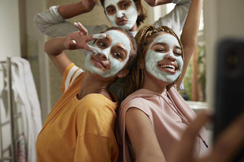 Happy young woman taking selfie with female friends wearing facial cream in bathroom at home