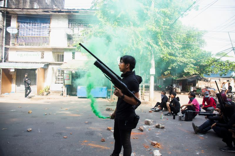 A protester holds a homemade pipe air gun during a protest against the military coup in Yangon