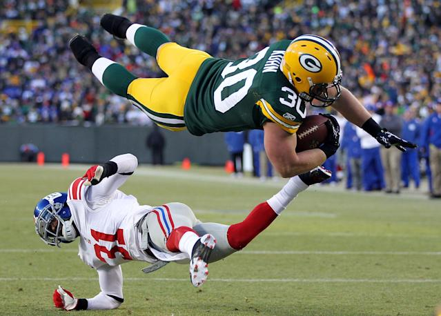GREEN BAY, WI - JANUARY 15: John Kuhn #30 of the Green Bay Packers dives in for the touchdown over Aaron Ross #31 of the New York Giants during their NFC Divisional playoff game at Lambeau Field on January 15, 2012 in Green Bay, Wisconsin. (Photo by Jamie Squire/Getty Images)