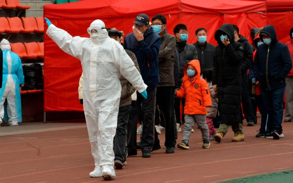 A worker wearing a protective suit leads residents to a makeshift Covid-19 testing centre in Tianjin - AFP