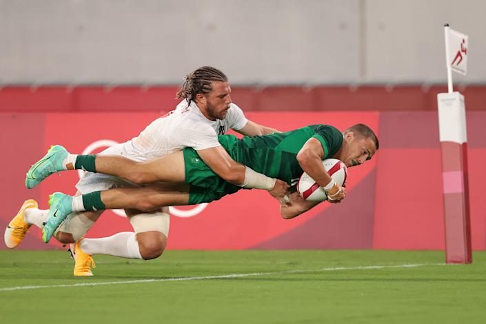 <p>CHOFU, JAPAN - JULY 26: Hugo Lennox of Team Ireland scores a try under pressure from Steve Tomasin of Team United States during the Men's Pool C Rugby Sevens match between United States and Ireland on day three of the Tokyo 2020 Olympic Games at Tokyo Stadium on July 26, 2021 in Chofu, Tokyo, Japan. (Photo by Dan Mullan/Getty Images)</p>