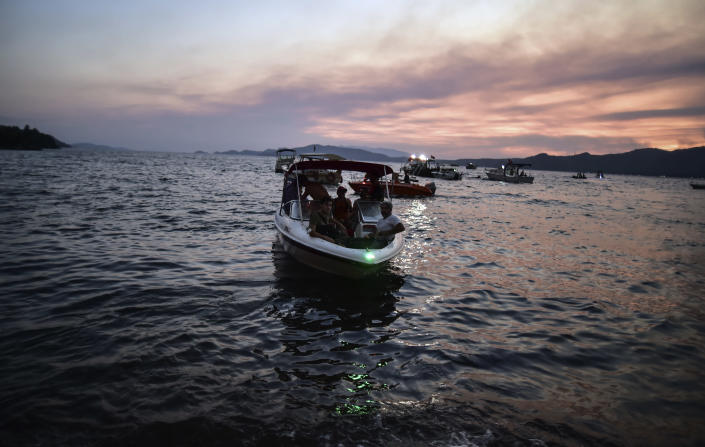 People leave with a boat as advancing fires rage Hisaronu area, Turkey, Monday, Aug. 2, 2021. For the sixth straight day, Turkish firefighters battled Monday to control the blazes that are tearing through forests near Turkey's beach destinations. Fed by strong winds and scorching temperatures, the fires that began Wednesday have left eight people dead. Residents and tourists have fled vacation resorts in flotillas of small boats or convoys of cars and trucks. (AP Photo)
