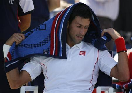 Djokovic of Serbia pauses during a break in play against Wawrinka of Switzerland during their men's semi-final match at the U.S. Open tennis championships in New York