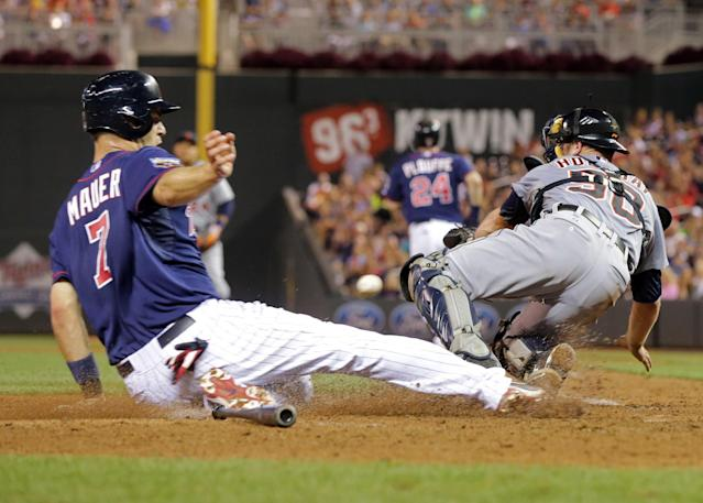Minnesota Twins' Joe Mauer, left, scores on Trevor Plouffe fielder's choice as Detroit Tigers catcher Bryan Holaday, right, tries to get the wide throw from third baseman Nick Castellanos allowing Twins' Kennys Vargas to score on an error by Castellanos in the sixth inning of a baseball game, Friday, Aug. 22, 2014, in Minneapolis. (AP Photo/Jim Mone)