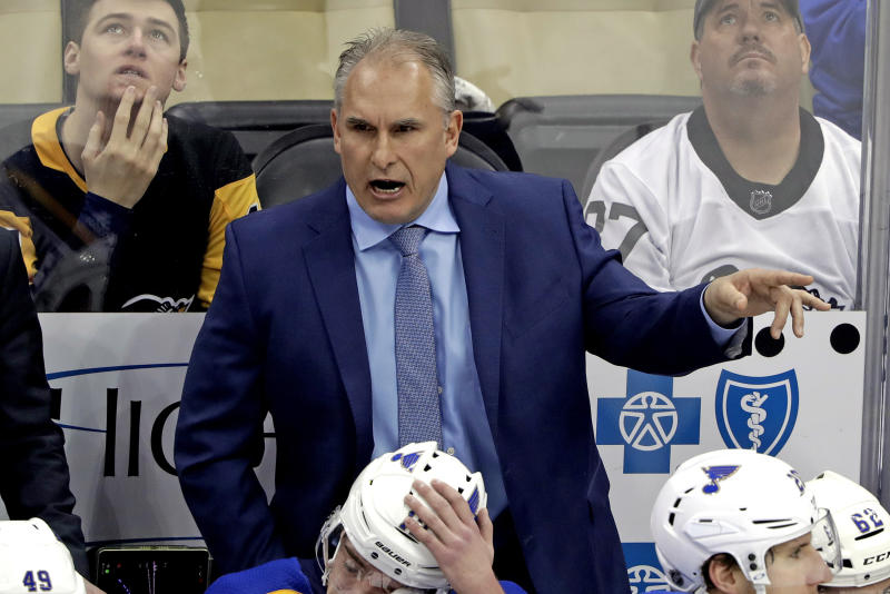 FILE - In this March 16, 2019, file photo, St. Louis Blues interim head coach Craig Berube gives instructions from behind his bench during the first period of an NHL hockey game against the Pittsburgh Penguins in Pittsburgh. Two roads diverged in a crazy world of hockey and brought them to this Stanley Cup Final. Cassidy has guided the Boston Bruins to this point a decade and a half after a disastrous tenure in Washington, and Berube took the St. Louis Blues from worst to their first final since 1970 several years after a short stint in Philadelphia. (AP Photo/Gene J. Puskar, File)