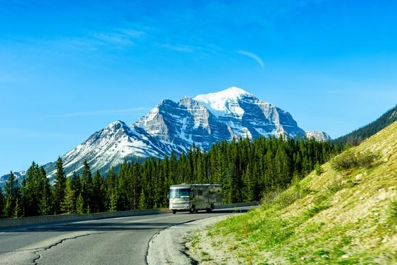 RV driving along a curving stretch of road with pine trees and a snowy mountain peak in the background
