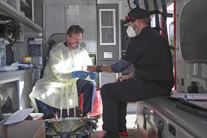 In this Saturday, May 9, 2020 photo, photographer Jason Vinlove, right, gets tested for COVID-19 antibodies before covering UFC 249 in Jacksonville, Florida. (AP Photo/John Raoux)