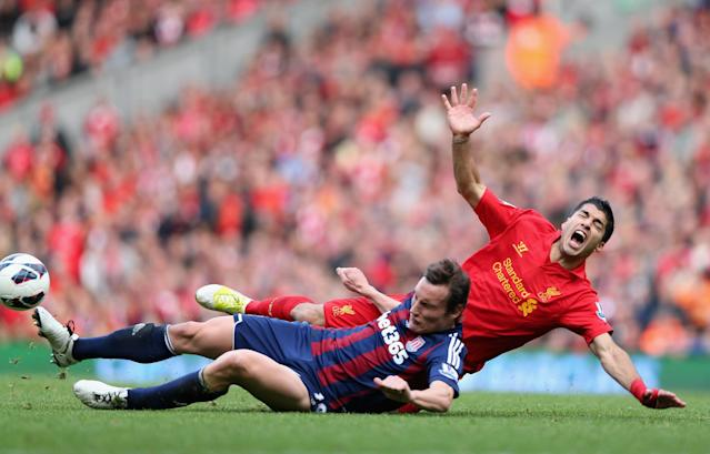 LIVERPOOL, ENGLAND - OCTOBER 07: Dean Whitehead of Stoke City tackles Luis Suarez of Liverpool during the Barclays Premier League match between Liverpool and Stoke City at Anfield on October 7, 2012 in Liverpool, England. (Photo by Clive Brunskill/Getty Images)