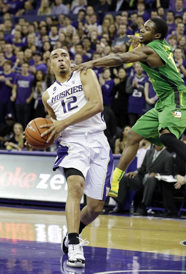 Washington guard Andrew Andrews (12) drives past Oregon guard Johnathan Loyd in the first half of an NCAA men's college basketball game Thursday, Jan. 23, 2014, in Seattle. (AP Photo/Elaine Thompson)