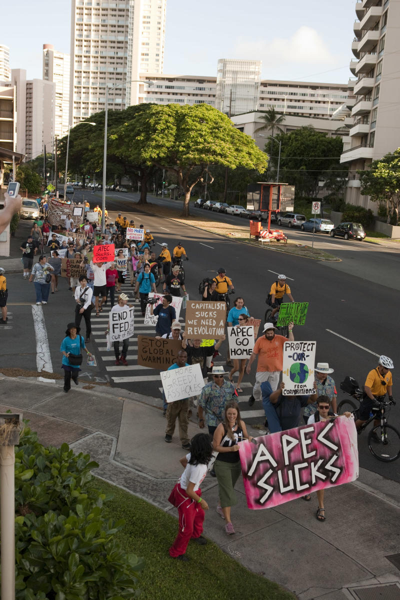Anti-APEC protesters march down Kalakaua Ave. towards Waikiki, Saturday, Nov. 12, 2011 in Honolulu.  The APEC Summit is being held in Oahu this weekend.  A few hundred protesters marched in the demonstration.  (AP Photo/ Marco Garcia)
