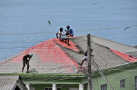 People clean volcanic ash from the red roof of a home after La Soufriere volcano erupted, in Wallilabou, on the western side of the Caribbean island of St. Vincent, Monday, April 12, 2021. (AP Photo/Orvil Samuel)
