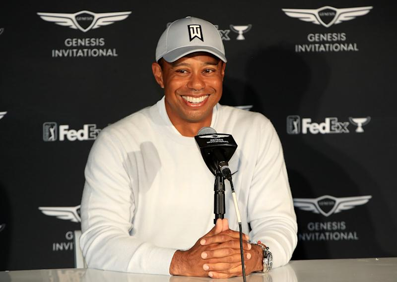 Tiger Woods smiles during a press conference.