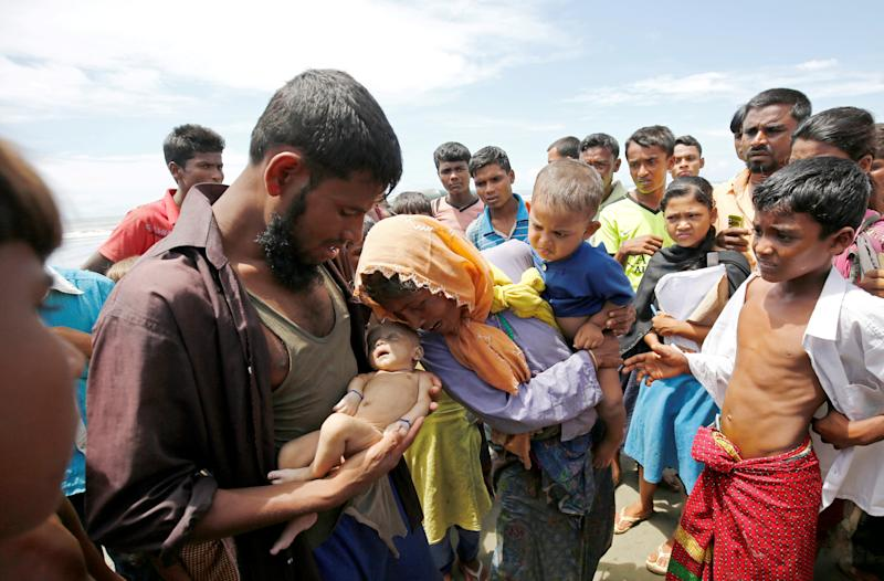 Nasir Ahmed cradles his dead son. (Mohammad Ponir Hossain / Reuters)