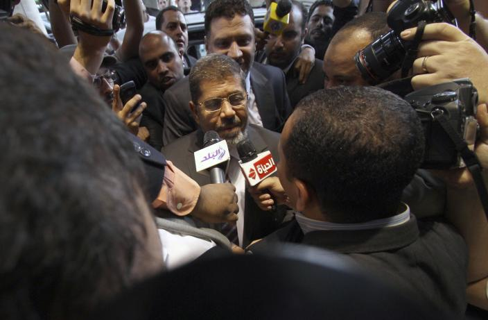 Mohammed Morsi, the Muslim Brotherhood's presidential candidate, is surrounded by reporters in Cairo, Egypt, Saturday, May 26, 2012. Results from the first round of voting have shown that the Muslim Brotherhood's candidate Mohammed Morsi and Hosni Mubarak's last prime minister Ahmed Shafiq will face each other in a June 16-17 runoff.(AP Photo/Ahmed Gomaa)