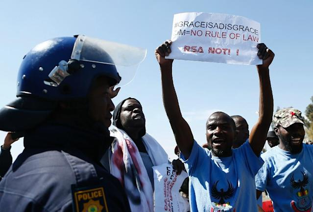 """Protesters gathered outside a summit of regional leaders in Pretoria which Zimbabwe's first lady had been due to attend, some waving signs reading """"Grace is a disgrace"""" (AFP Photo/Phill Magakoe)"""