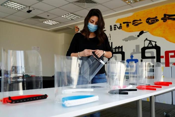 The Giza Systems Education Foundation make protective face shield for use by medical professionals treating COVID-19 coronavirus patients (AFP Photo/Khaled DESOUKI)