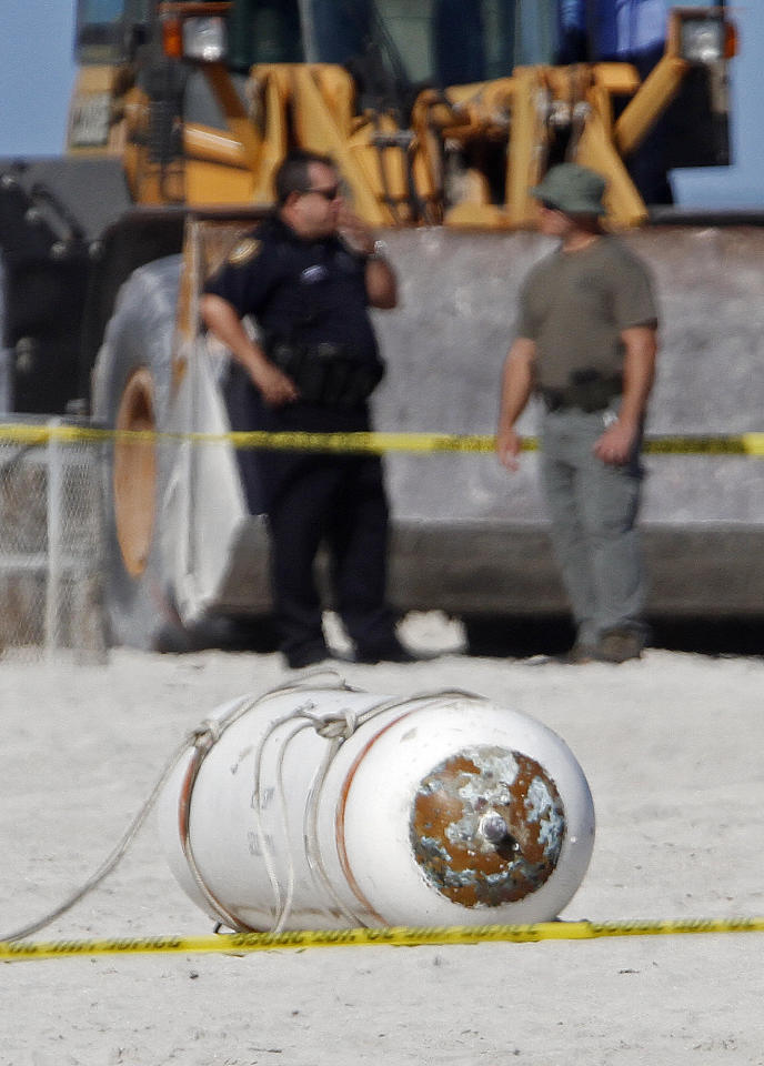 "A live Navy training mine that washed ashore is shown at Miami Beach, Fla., Monday, Dec. 5, 2011. A perimeter was established once Fire Rescue arrived at the scene Monday morning. Spokesman Jesus Sola says photos were taken and sent to the Navy, which will remove the device that is six feet long and 2 feet in diameter. Sola says the mine is ""still live"" but it is not as explosive as a regular mine. (AP Photo/Alan Diaz)"