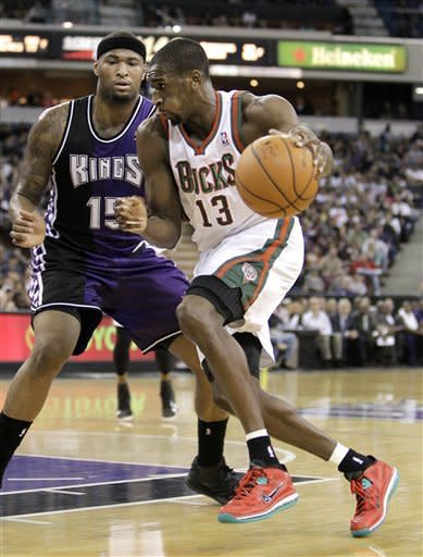 Milwaukee Bucks center Ekpe Udoh, right, drives against Sacramento Kings center DeMarcus Cousins during the first quarter of an NBA basketball game in Sacramento, Calif., Sunday, March 10, 2013.(AP Photo/Rich Pedroncelli)
