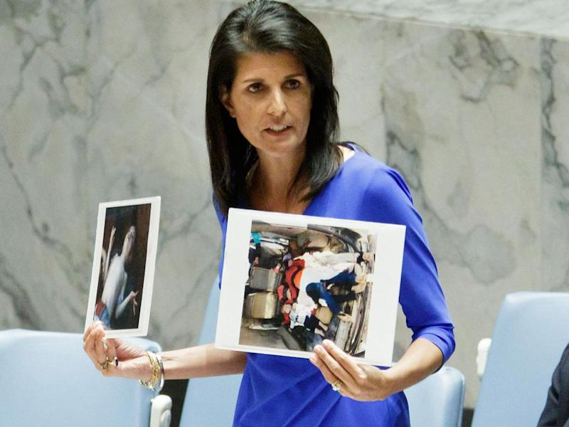 Nikki Haley, the United States' Ambassador to the United Nations, holds up images of victims of a chemical attack in Syria (EPA)