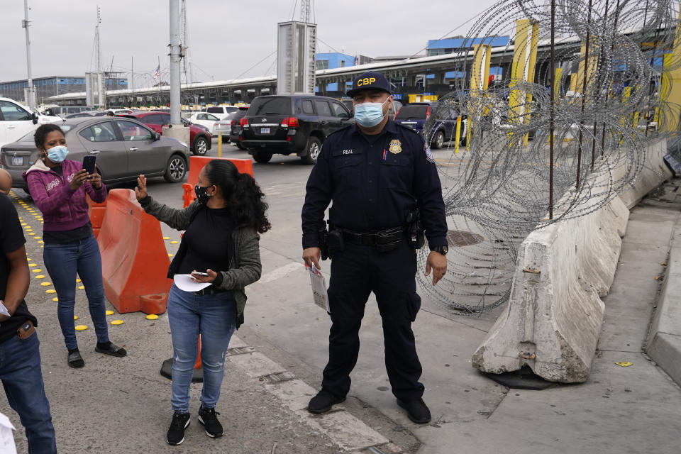 Lizeth Morales, of Honduras, waves to a friend as she crosses into the United States to begin the asylum process Monday, July 5, 2021, in Tijuana, Mexico. Dozens of people are allowed into the U.S. twice a day at a San Diego border crossing, part of a system that the Biden administration cobbled together to start opening back up the asylum system in the U.S. Immigration advocates have been tasked with choosing which migrants can apply for a limited number of slots to claim humanitarian protection. (AP Photo/Gregory Bull)