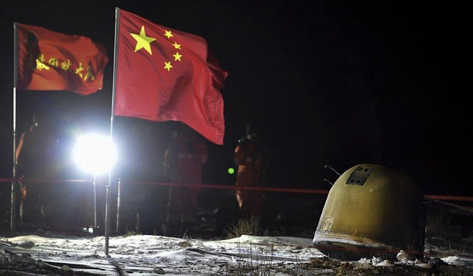 Recovery crew members film the capsule of the Chang'e 5 probe after its successful landing in Siziwang district, north China's Inner Mongolia Autonomous Region. Photo: Xinhua