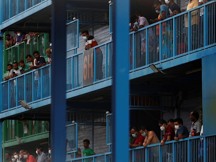 <br>Migrant workers look out from their balconies at Punggol S11 dormitory in Singapore on April 6, 2020.
