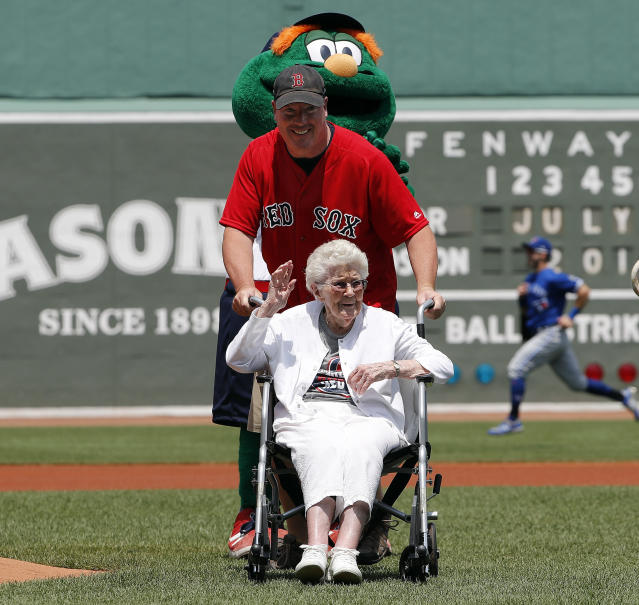 106-year-old Juliette Campbell waves as she is pushed off the field by her grandson Craig Campbell after placing the game ball on the mound before the baseball game between the Boston Red Sox and the Toronto Blue Jays Saturday, July 14, 2018, in Boston. (AP Photo/Winslow Townson)