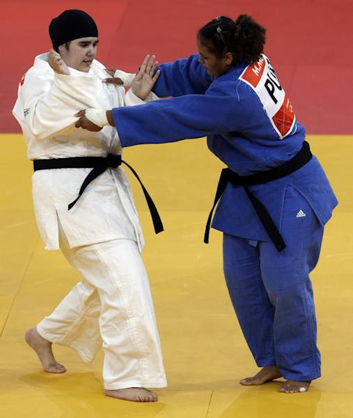 FILE - In this Friday, Aug. 3, 2012 file photo, Saudi Arabia's Wojdan Shahrkani and Puerto Rico's Melissa Mojica compete during the women's 78-kg judo competition at the 2012 Summer Olympics in London. Saudi Arabia's official press agency says the Education Ministry has allowed private female schools to hold sports activities within the Islamic Sharia laws. SPA said Saturday, May 4, 2013 that the ministry issued directives ordering private female schools to provide appropriate places and equipment for such activities, adhere to wearing decent dress and that Saudi women teachers should be given priority in supervising these activities. (AP Photo/Mike Groll, File)