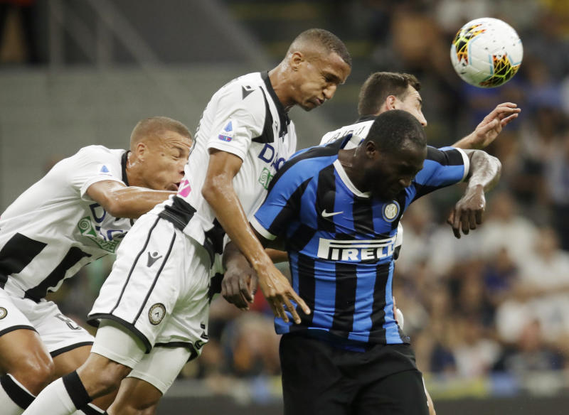 Inter Milan's Romelu Lukaku, right, heads the ball flanked by Udinese's Mato Jajalo, Rodrigo Becao, center, and Udinese's Sebastien De Maio, left, during a Serie A soccer match between Inter Milan and Udinese, at the San Siro stadium in Milan, Italy, Saturday, Sept. 14, 2019. (AP Photo/Luca Bruno)
