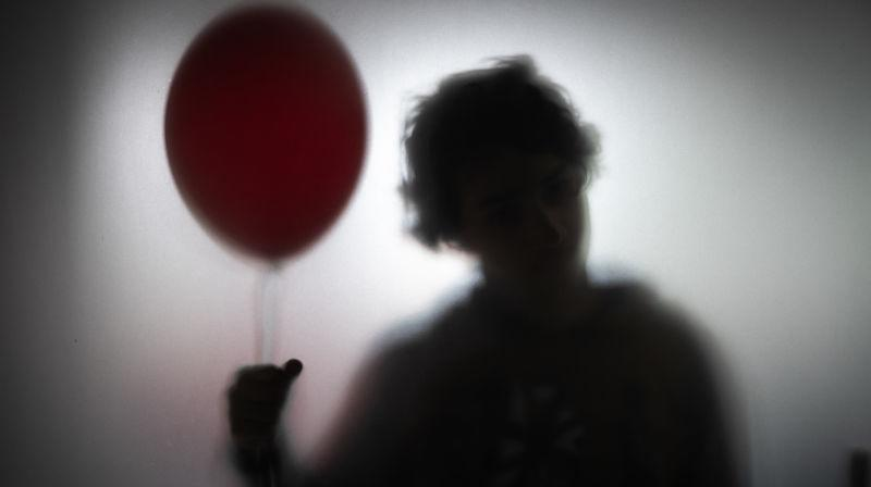 Foggy silhouette of creepy person holding a red balloon