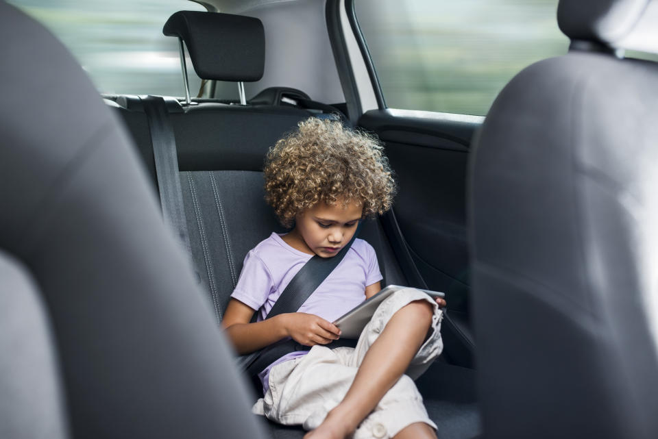 Little girl using digital tablet while sitting on car's back seat