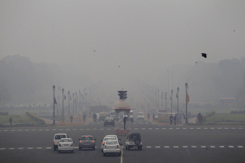 Smog and fog envelop the Rajpath, the ceremonial boulevard, behind, as a police man, center, controls traffic in the morning in New Delhi, India, Wednesday, Feb. 5, 2014. On bad days in India's congested capital, the air is so murky it slows traffic to a crawl because visibility is so poor. Conversations are punctuated with rasping coughs. Weak bands of sunlight filter through a grainy sky. (AP Photo/Tsering Topgyal)